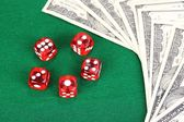 Red dices and dollars on green background — Stock Photo