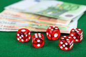 Red dices and money, on green background — Stock Photo