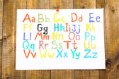 Alphabet watercolors on wooden background — 图库照片
