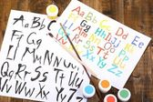 Alphabet watercolors on wooden background — Stok fotoğraf