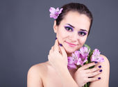 Beautiful young woman with flowers on gray background — Stockfoto