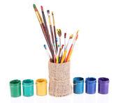 Escovas com tintas em vaso isolado no branco — Fotografia Stock