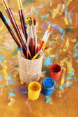 Many brushes in paints on multicolor wooden background — Stock fotografie