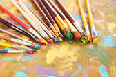 Many brushes in paints on multicolor wooden background — Stock Photo