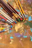 Many brushes in paints on multicolor wooden background — Stok fotoğraf