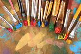 Many brushes in paints on multicolor wooden background — Zdjęcie stockowe