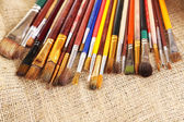 Many brushes in paints on sackcloth background — Стоковое фото