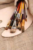 Many brushes in paints on sackcloth background — Stok fotoğraf