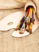 Many brushes in paints on sackcloth background — Foto de Stock