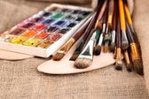 Composition with brushes, watercolors on wooden palette, isolated on white — Stock Photo