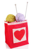 Woolen balls of yarn and wooden knitting needles in rustic craft bag, isolated on white — Stock Photo