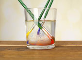 Brushes with color paint in glass of water, on wooden table — Stock Photo