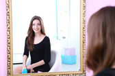 Young beautiful woman sitting front of mirror in room — Stock Photo