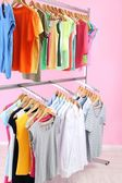 Różne ubrania na wieszakach, na tle różowy — Zdjęcie stockowe