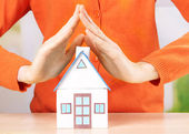 Little paper house in hand close-up, on light background — Foto de Stock