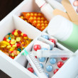 Medical pills, ampules in wooden box, on color background — Stock Photo