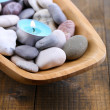 Wooden bowl with Spa stones, sea shells and candles on wooden background — Stock Photo #43221897