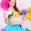 Beautiful young woman in petty skirt holding basket of flowers on decorative background — Stock Photo #43225599