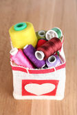 Colorful bobbins of thread  in bag, on wooden background — Stock Photo
