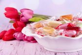 Tasty candies in bowl with flowers on table on bright background — ストック写真