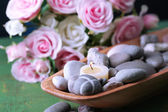 Wooden bowl with spa stones and candles on wooden  table, on flowers background — Stock Photo