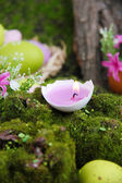 Conceptual Easter composition. Burning candle in egg, Easter eggs and flowers on green grass background, close-up — Stock Photo