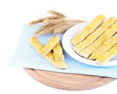 Tasty bread sticks on plate on color napkin, isolated on white — Stock Photo