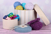 Decorative boxes with colorful skeins of thread on table on bright background — Stock Photo