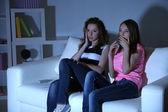 Jóvenes amigas viendo la película de terror en la casa de ennegrecerse — Foto de Stock