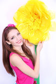 Beautiful young woman in petty skirt with big flower close up — Stock Photo
