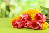 Pink and yellow tulips on wooden table on natural background — Stock Photo