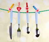 Cutlery dried on rope on bright background — Stock Photo