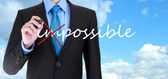 Businessman turning word impossible into possible on sky background — Stock Photo