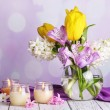 Flowers in vase with candles on table on bright background — Stock Photo