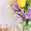 Flowers in vase with candles on table on wooden background — Stock Photo