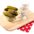 Glasses of vodka and salted cucumbers on wooden board isolated on white — Stock Photo #43366437