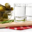 Glasses of vodka and salted cucumbers on wooden board isolated on white — Stock Photo #43366503