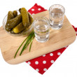 Glasses of vodka and salted cucumbers on wooden board isolated on white — Stock Photo #43366505
