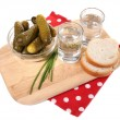 Glasses of vodka and salted cucumbers on wooden board isolated on white — Stock Photo #43366533