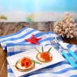 Pancakes with red caviar, salmon and mayo, green onion, on plate, on color napkin, on wooden  table, on bright background — Stock Photo #43367889