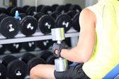 Guy with dumbbells on gym background close-up — Stok fotoğraf