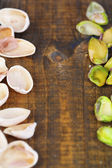 Peeled pistachios nuts on wooden background — Stock Photo