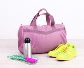 Sports bag with sports equipment in gymnasium — Stock Photo