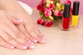 Beautiful woman hands with french manicure and flowers on table close up — Photo