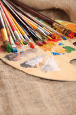 Composition with brushes on used wooden palette, on wooden background — Stock Photo
