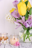 Flowers in vase with candles on table on wooden background — Stockfoto