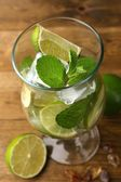 Ingredients for lemonade in glass, on wooden table — Foto Stock