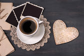 Composition with coffee cup, letters and old blank photos, on wooden background — Stock Photo