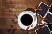 Coffee cup and old blank photos and spices, on wooden background — Stock Photo