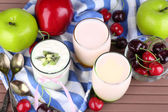 Delicious yogurt with fruits tastes in glasses and fresh fruits on color napkin, on wooden background — Foto de Stock